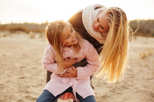 Красивая мама играет со своей маленькой дочерью