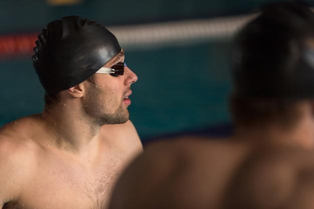 Крупным планом пловец в кепке и плавательные очки