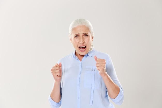 Фото радостной пожилой женщины, поддерживающей что-то