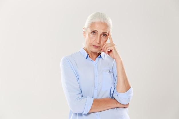 Фото мыслящей старушки в синей рубашке