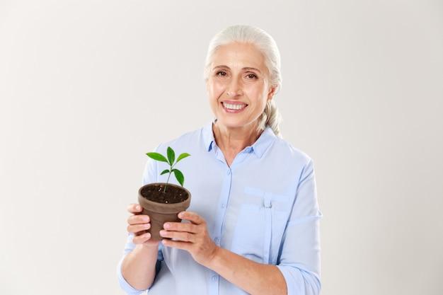 Портрет счастливой старшей женщины, держа горшок с зеленым растением