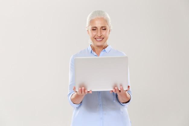 Зрелая женщина держа и используя изолированный портативный компьютер