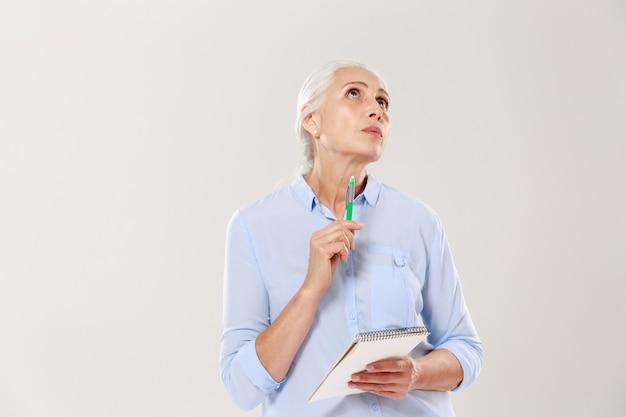 Вдумчивый женщина с блокнот и ручка мышления и глядя вверх