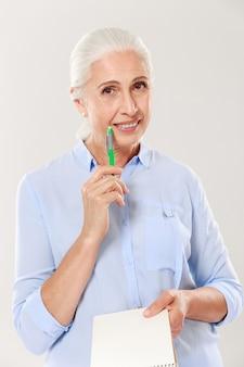 Счастливая женщина с ручкой и тетрадью смотря и усмехаясь