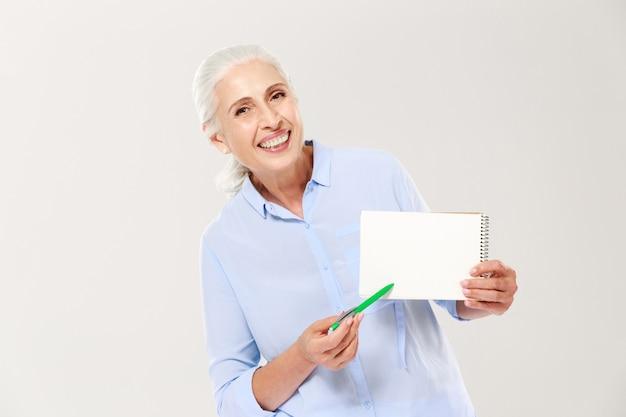 Усмехаясь зрелая женщина показывая тетрадь с космосом экземпляра для изолированного текста