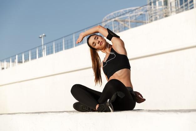 Сконцентрированная молодая спортивная женщина делает спортивные упражнения на растяжку.