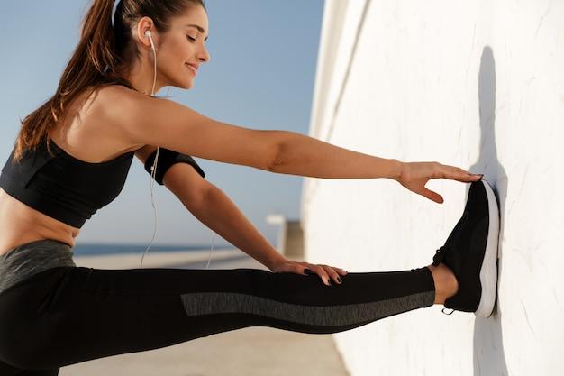 Улыбающаяся женщина делает упражнения во время тренировки