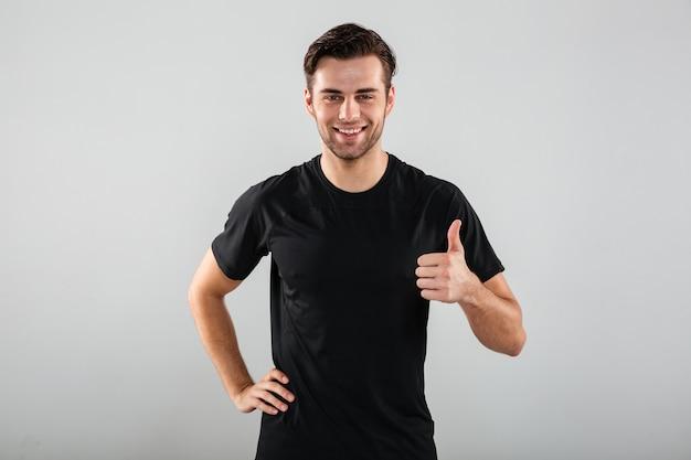 陽気な若いスポーツ男が親指ジェスチャーを示すポーズします。