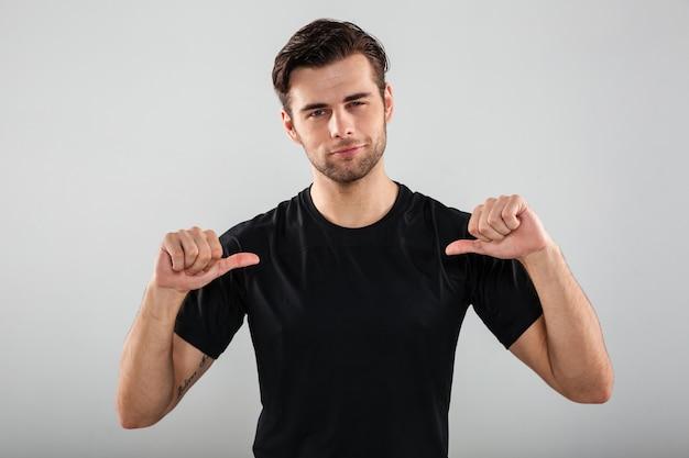 自分を指しているハンサムな若いスポーツ男。