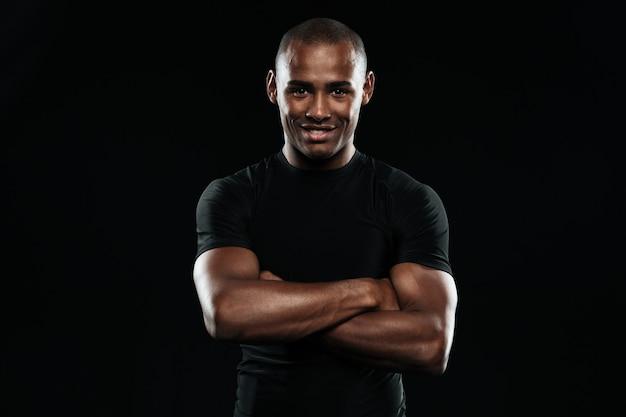 Усмехаясь афро американский спорт укомплектовывает личным составом с оружиями сложил смотреть камеру
