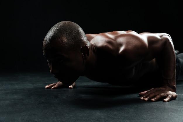Крупным планом портрет афро-американского спортивного человека, с красивым мускулистым телом, делая упражнения выжимания в упоре на полу