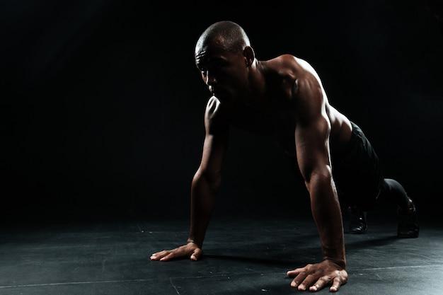 Портрет человека афро-американского спорта делает упражнение отжимания