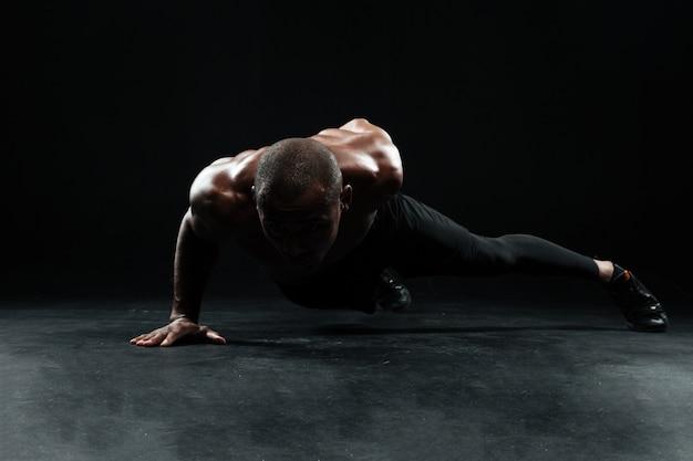 Афро-американский спортсмен с красивым мускулистым телом делает отжимания одной рукой на полу