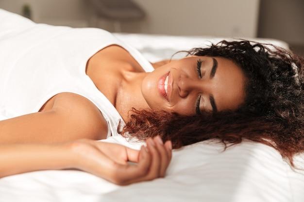 アフリカの若い女性がベッドで日光浴を楽しむ