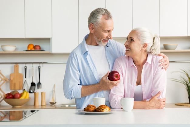 台所で立っている笑顔の成熟した愛情のあるカップル家族