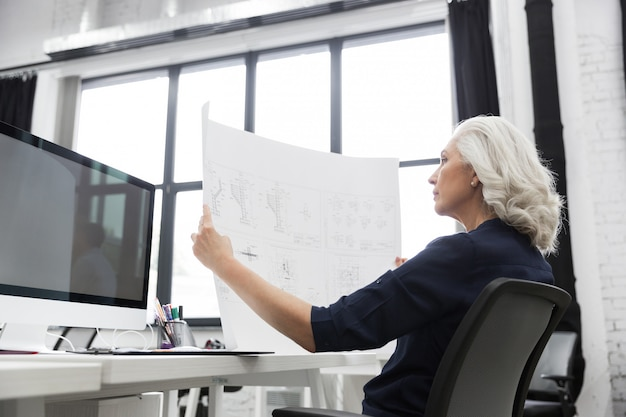 彼女の前で開催されたグラフを分析する成熟したビジネス女性