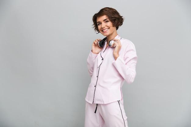 ヘッドフォンでパジャマ姿で陽気な笑みを浮かべて少女の肖像画