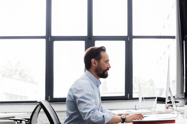 コンピューターで作業してビジネスの男性の側面図