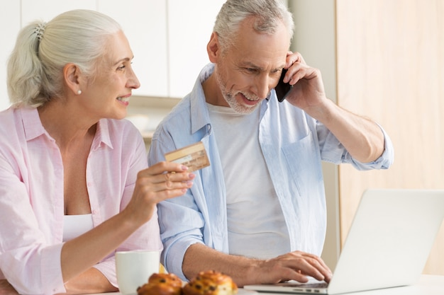 Усмехаясь зрелая любящая семья пар используя компьтер-книжку держа кредитную карточку.