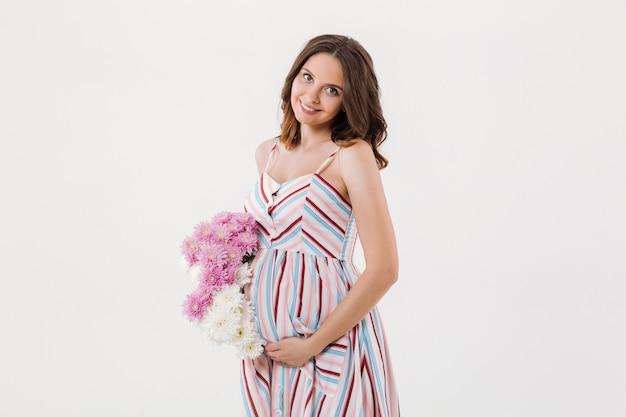 Веселая беременная женщина, держащая цветы.