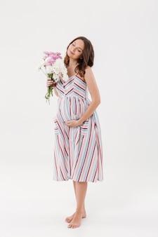 目を閉じて花を持って陽気な妊娠中の女性。