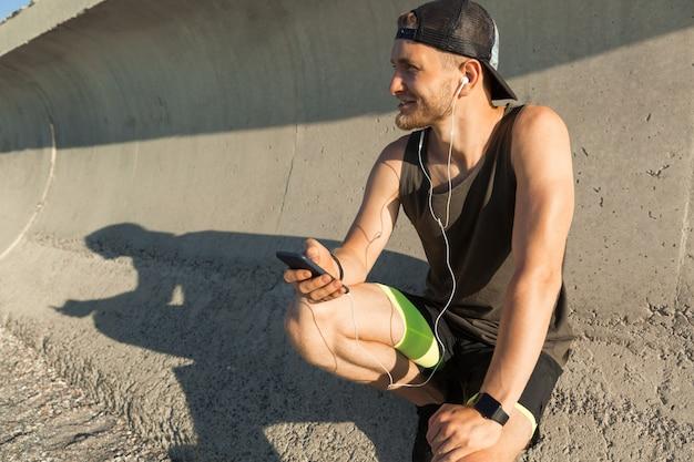 イヤホンで音楽を聴く運動の若いスポーツマン