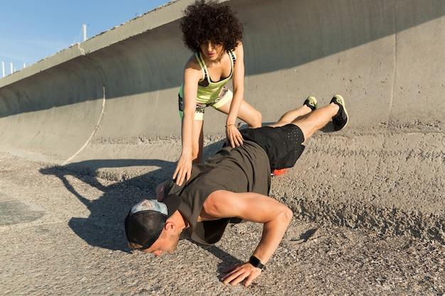 Молодые здоровые пары фитнеса делая тренировки спорта