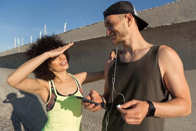 屋外のイヤホンで音楽を聴く若いフィットネスカップル