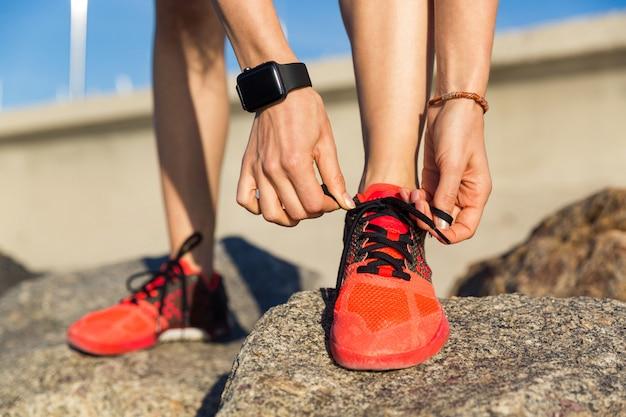 Крупным планом мужской бегун, связывая его шнурки