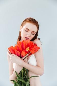 チューリップの花束を保持している若い美しい女性の肖像画