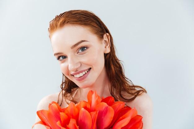 Крупным планом портрет рыжеволосой женщины, держащей цветы тюльпана