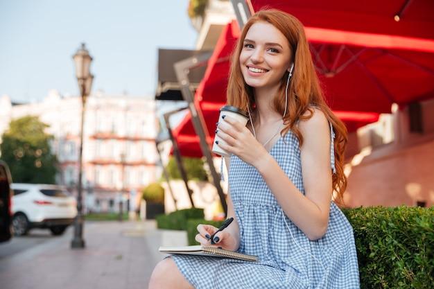 イヤホンで幸せな陽気な赤毛の女の子