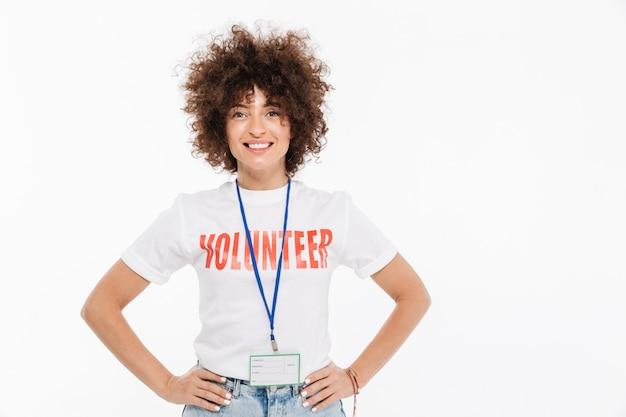 Улыбающаяся случайная женщина, одетая в волонтерскую футболку со значком