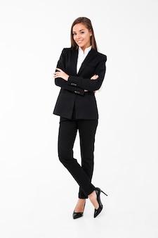 Удивительная веселая деловая женщина, стоя со скрещенными руками