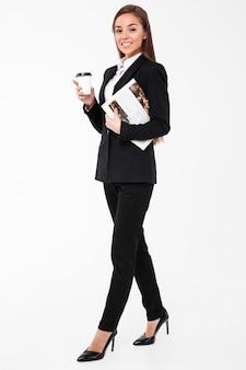コーヒーを飲みながら新聞を保持している陽気なビジネス女性。