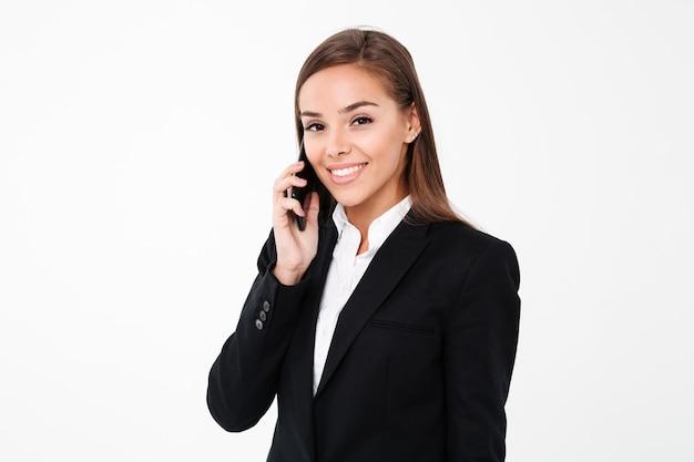 Счастливая милая коммерсантка говоря по телефону.
