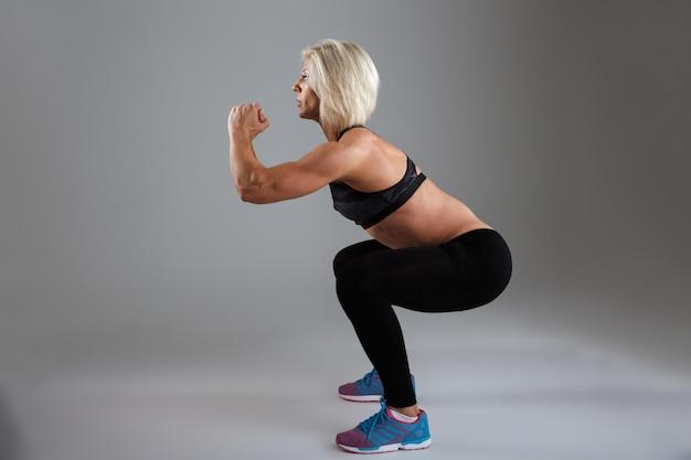 Вид сбоку концентрированной мускулистой взрослой спортсменки