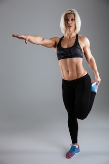 筋肉の大人のスポーツウーマンの完全な長さの肖像画