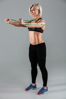 集中した筋肉の大人のスポーツウーマンの完全な長さの肖像画