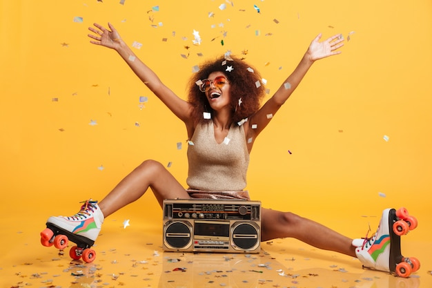 Очаровательная молодая африканская женщина в ретро одежде и роликовых коньках, бросающая конфетти, сидя с бумбоксом