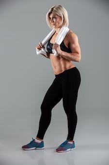 魅力的な筋肉の大人の女性の完全な長さの肖像画