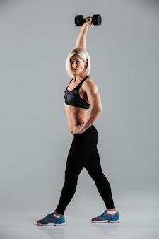 集中した筋肉のスポーツウーマンの完全な長さの肖像画