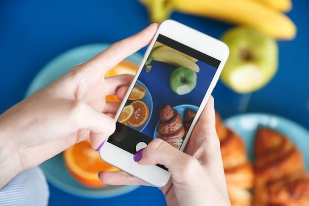 女性の手が食べ物で携帯電話で写真を撮る
