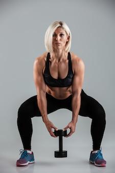 Полная длина портрет концентрированной мускулистой взрослой спортсменки