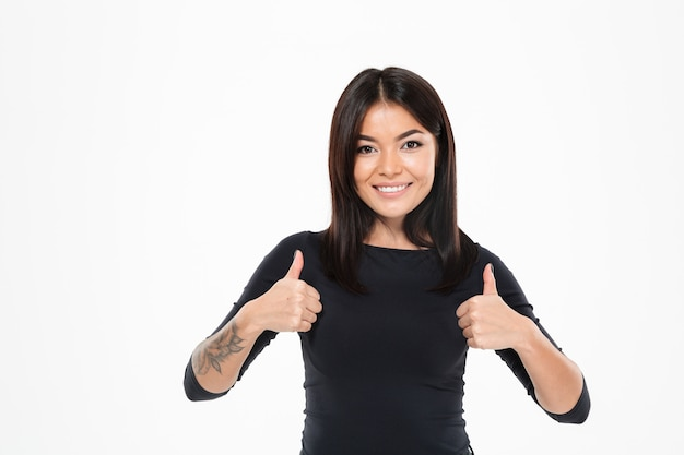 Счастливая молодая азиатская дама показывая большие пальцы руки вверх.
