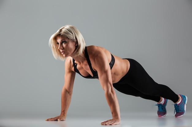 やる気のある筋肉の大人のスポーツウーマンの完全な長さの肖像画