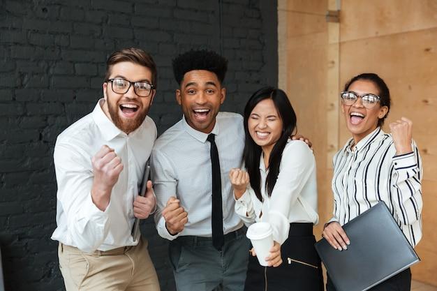 幸せな興奮して若いビジネス部門の同僚は、勝者のジェスチャーを作ります。