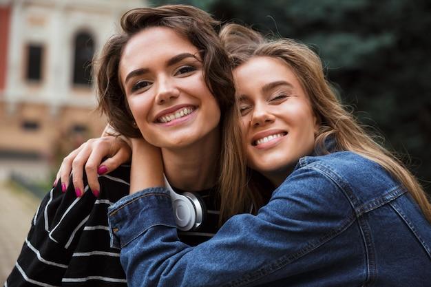 Две счастливые молодые девочки-подростки обнимаются