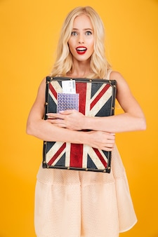 英国のプリントスーツケースを持ってショックを受けた若いブロンドの女性