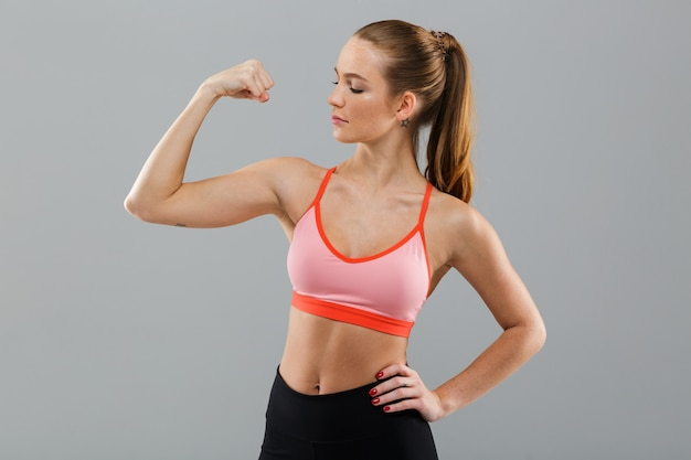 Удивительная молодая спортивная женщина, показывающая бицепс.